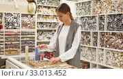 Купить «Skillful young seamstress looking for buttons for sewing clothes in haberdasher shop», видеоролик № 33013452, снято 3 апреля 2020 г. (c) Яков Филимонов / Фотобанк Лори