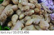 Купить «Fresh ginger root on showcase of greengrocery shop for sale to customers», видеоролик № 33013456, снято 20 февраля 2020 г. (c) Яков Филимонов / Фотобанк Лори