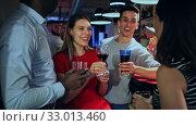 Купить «Happy women and men with cocktail chatting at bar counter in night club», видеоролик № 33013460, снято 21 февраля 2020 г. (c) Яков Филимонов / Фотобанк Лори