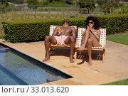 Купить «Young couple relaxing near swimming pool on a sunny day», фото № 33013620, снято 28 ноября 2019 г. (c) Wavebreak Media / Фотобанк Лори
