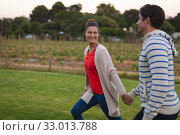 Купить «Happy young couple walking in the garden», фото № 33013788, снято 28 ноября 2019 г. (c) Wavebreak Media / Фотобанк Лори