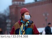 Купить «Женщина в медицинской маске на Красной площади в городе Москве во время эпидемии коронавируса в Китае», фото № 33014368, снято 31 января 2020 г. (c) Николай Винокуров / Фотобанк Лори