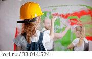 Купить «Little girl in overalls and a yellow helmet is telling parents where to paint the wall», видеоролик № 33014524, снято 3 июня 2020 г. (c) Константин Шишкин / Фотобанк Лори