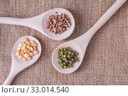Three wooden spoons with cereals buckwheat, mung beans and peas on burlap on the table, top view. Стоковое фото, фотограф Катерина Белякина / Фотобанк Лори