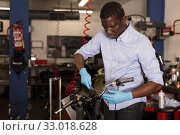 Купить «Confident afro american worker using his tools for repairing in motorcycle workshop», фото № 33018628, снято 22 ноября 2019 г. (c) Яков Филимонов / Фотобанк Лори