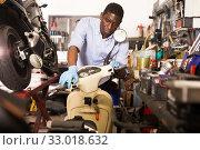 Male afro american worker repairing scooter in motorcycle workshop. Стоковое фото, фотограф Яков Филимонов / Фотобанк Лори