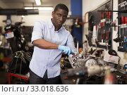 Portrait of man master who is repairing motobike in the workshop. Стоковое фото, фотограф Яков Филимонов / Фотобанк Лори
