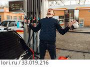 Depressed man cries on gas station, fuel filling. Стоковое фото, фотограф Tryapitsyn Sergiy / Фотобанк Лори