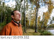 Мужчина в оранжевой кофте на фоне берега реки с березовой рощей. Осенний лес. Стоковое фото, фотограф Elizaveta Kharicheva / Фотобанк Лори