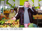 Купить «Glad man solving questions by phone in store», фото № 33020608, снято 13 февраля 2018 г. (c) Яков Филимонов / Фотобанк Лори