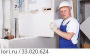 Купить «Builder engaged in drywall installation», фото № 33020624, снято 28 мая 2018 г. (c) Яков Филимонов / Фотобанк Лори
