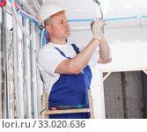 Купить «Electrician mounting electrical wiring», фото № 33020636, снято 28 мая 2018 г. (c) Яков Филимонов / Фотобанк Лори