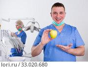 Купить «Smiling male dentist with apple at dental clinic», фото № 33020680, снято 1 марта 2018 г. (c) Яков Филимонов / Фотобанк Лори