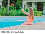 Купить «Adorable little girl swimming at outdoor swimming pool», фото № 33021120, снято 15 февраля 2016 г. (c) Дмитрий Травников / Фотобанк Лори