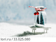Christmas ornaments of glass jar with striped ribbon , bells and fir trees inside on snow background. Стоковое фото, фотограф Zoonar.com/Ivan Mikhaylov / easy Fotostock / Фотобанк Лори