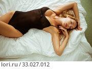 Купить «Beautiful sexy slim girl with a perfect figure lies on a white sheet in black bodysuit», фото № 33027012, снято 9 сентября 2017 г. (c) katalinks / Фотобанк Лори