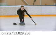 Купить «Curling training - a young woman with long hair pushes off from the stand with a stone biter», видеоролик № 33029256, снято 5 июня 2020 г. (c) Константин Шишкин / Фотобанк Лори
