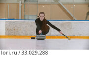 Купить «Curling training - a young woman with long hair pushes off from the stand - leading the stone biter with blue handle», видеоролик № 33029288, снято 5 июня 2020 г. (c) Константин Шишкин / Фотобанк Лори