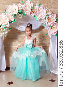 Portrait of girl princess in turquoise dress with diamond diadem on the background of flower arch. Стоковое фото, фотограф Евгений Ткачёв / Фотобанк Лори