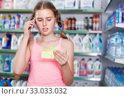 Купить «Teenage girl looking goods with shopping list and phone in shop», фото № 33033032, снято 4 июля 2018 г. (c) Яков Филимонов / Фотобанк Лори
