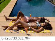 Купить «Young couple relaxing near swimming pool on a sunny day», фото № 33033704, снято 28 ноября 2019 г. (c) Wavebreak Media / Фотобанк Лори