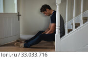Worried man sitting in the stairs at home. Стоковое фото, агентство Wavebreak Media / Фотобанк Лори