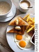 Купить «Fried eggs with toast and french fries for breakfast», фото № 33034088, снято 6 июля 2019 г. (c) Володина Ольга / Фотобанк Лори