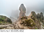Купить «Nature mountain landscape of Canary Island with rock peak enveloping by dense fog», фото № 33035432, снято 2 апреля 2020 г. (c) easy Fotostock / Фотобанк Лори