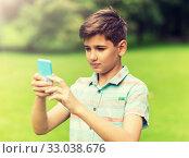 Купить «boy with smartphone playing game in summer park», фото № 33038676, снято 24 июля 2016 г. (c) Syda Productions / Фотобанк Лори