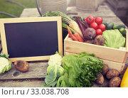 Купить «close up of vegetables with chalkboard on farm», фото № 33038708, снято 25 августа 2016 г. (c) Syda Productions / Фотобанк Лори