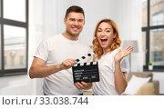 Купить «happy couple in white t-shirts with clapperboard», фото № 33038744, снято 6 октября 2019 г. (c) Syda Productions / Фотобанк Лори