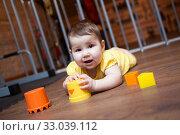 Little baby playing with plastic blocks of pyramid while lying on hardwood at home. Стоковое фото, фотограф Кекяляйнен Андрей / Фотобанк Лори