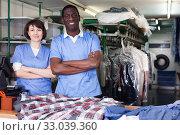 Купить «Two confident workers of dry cleaner», фото № 33039360, снято 15 января 2019 г. (c) Яков Филимонов / Фотобанк Лори