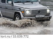 Mercedes-Benz G-Wagen driving on flooded street road over deep muddy puddle (2018 год). Редакционное фото, фотограф А. А. Пирагис / Фотобанк Лори