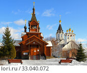 Two churches, old wooden and new stone, of Holy Apostles Constantine and Elena in winter. Moscow, Russia (2020 год). Редакционное фото, фотограф Валерия Попова / Фотобанк Лори