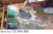 Купить «Creative painter mixes palette of oil paints in palette on easel. Close-up view», видеоролик № 33044480, снято 30 августа 2019 г. (c) А. А. Пирагис / Фотобанк Лори