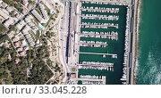 Купить «Picturesque aerial view of Mediterranean coastal town of Torredembarra with yachts moored in harbor, Tarragona, Spain», видеоролик № 33045228, снято 18 марта 2019 г. (c) Яков Филимонов / Фотобанк Лори