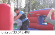 Купить «Two cheerful men having funny battle by big boxing gloves on inflatable arena at amusement park», видеоролик № 33045408, снято 12 ноября 2019 г. (c) Яков Филимонов / Фотобанк Лори