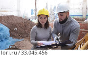 Купить «Two confident engineers discussing blueprint while standing at construction site», видеоролик № 33045456, снято 11 декабря 2019 г. (c) Яков Филимонов / Фотобанк Лори