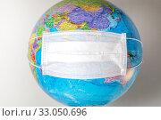 Купить «Глобус с надетой медицинской маской на белом фоне (концепция - экология, глобальная эпидемия)», фото № 33050696, снято 8 февраля 2020 г. (c) Николай Винокуров / Фотобанк Лори