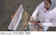 Купить «Female artist draws brush oil paints on canvas autumn mountains landscape», видеоролик № 33050700, снято 30 августа 2019 г. (c) А. А. Пирагис / Фотобанк Лори