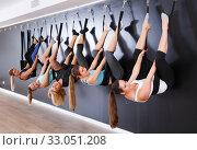 Купить «Girls practicing wall yoga with straps in studio», фото № 33051208, снято 29 января 2018 г. (c) Яков Филимонов / Фотобанк Лори