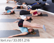 Купить «Women exercising yoga poses in fitness center», фото № 33051216, снято 29 января 2018 г. (c) Яков Филимонов / Фотобанк Лори