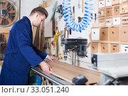 Купить «Man laying board to drill», фото № 33051240, снято 7 ноября 2016 г. (c) Яков Филимонов / Фотобанк Лори