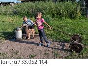 Купить «Мальчик набирает воду в флягу, девочка стоит с тележкой у деревенской колонки летом», фото № 33052104, снято 2 августа 2019 г. (c) Светлана Попова / Фотобанк Лори