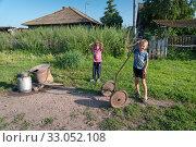 Купить «Мальчик с девочкой пришли к деревенской колонке за водой», фото № 33052108, снято 2 августа 2019 г. (c) Светлана Попова / Фотобанк Лори