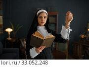 Купить «Young nun in a cassock holds book», фото № 33052248, снято 14 ноября 2019 г. (c) Tryapitsyn Sergiy / Фотобанк Лори