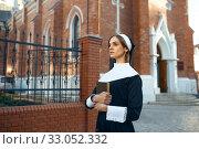 Купить «Young nun in a cassock, church on background», фото № 33052332, снято 14 ноября 2019 г. (c) Tryapitsyn Sergiy / Фотобанк Лори