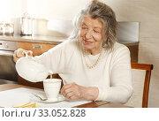 Купить «An old woman pours herself a cup of tea», фото № 33052828, снято 2 февраля 2020 г. (c) Алексей Кузнецов / Фотобанк Лори