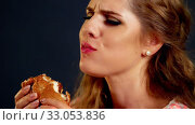 Купить «Girl eating hamburger. Hungry young woman gobbles with appetite.», видеоролик № 33053836, снято 28 декабря 2019 г. (c) Gennadiy Poznyakov / Фотобанк Лори